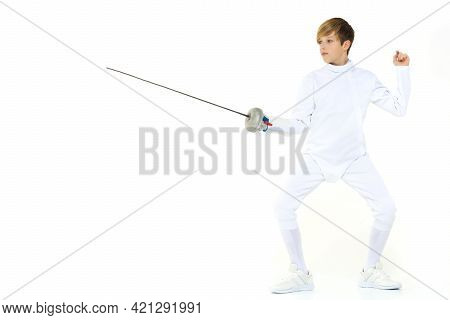 Boy Fencer Standing In Attacking Pose. Junior Boy Wearing White Fencing Suit Posing With Rapier Agai