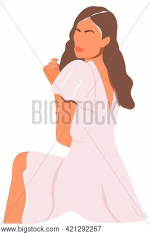 The Girl Hugs Herself And Sits In A Half-turn. Minimalist Portrait Of A Young Beautiful Woman With L