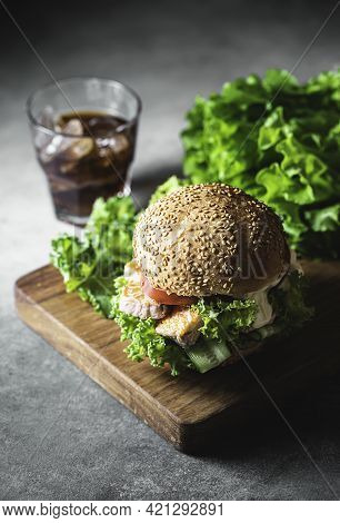 Delicious Salmon Burger, Served On Wooden Board . Fishburger With Fresh Salad, Fresh Vegetables And