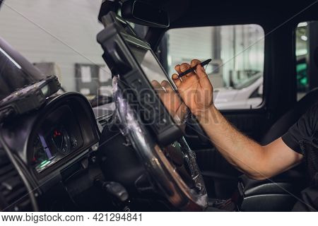 Mid Section Of Mechanic Holding A Diagnostic Tool.