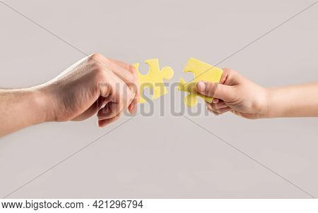 Puzzles. Hand Of The Child And Hand Of Mother Fold Puzzle, Closeup. Hands Hold Puzzles. Solution Of