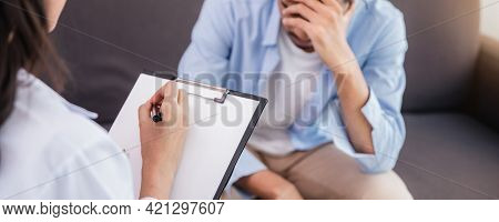Asian Woman Professional Psychologist Doctor Giving The Consult To Man Patients In Room Of House Or