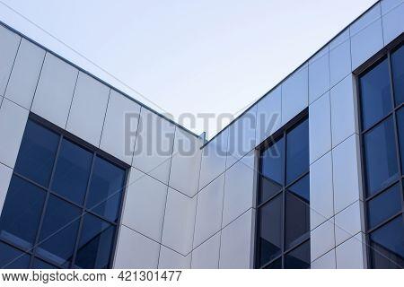 Modern Office Building Against The Sky. Facade Of A Business Building. Office Building Windows.