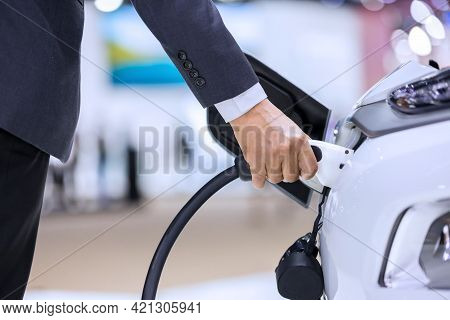 Hand Holding Electric Car Charger. Electric Vehicle Ev Charging Station And Charger. Human Hand Is H