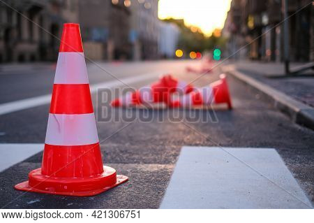 Bright Orange Traffic Cones Standing In A Row On Dark Asphalt In The City. Road Works. Selective Foc