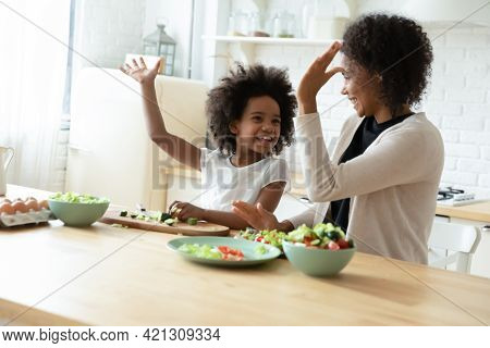 Happy African American Mom And Daughter Give High Five Cooking