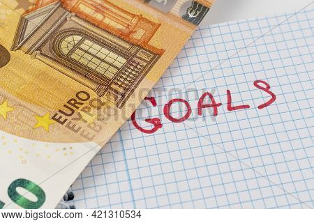 Word Goals Is Written In Red On A Checkered Paper Notepad. Fifty Euro Banknote Opens An Inscription