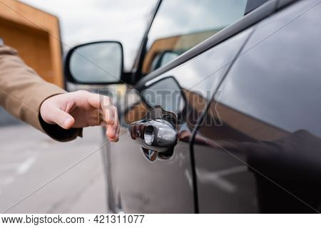 Cropped View Of Male Hand Reaching Door Of Black Car On Parking.
