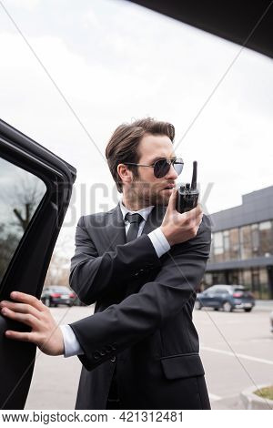 Bearded Bodyguard In Suit And Sunglasses Using Walkie Talkie Near Car.
