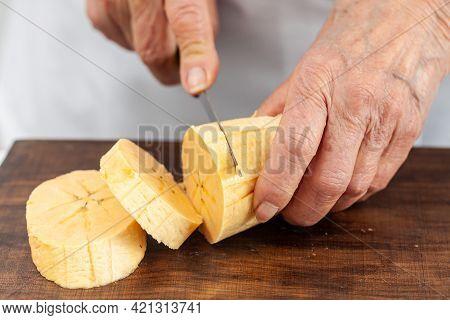 Closeup Of A Senior Woman Hands While Cuts A Ripe Plantain