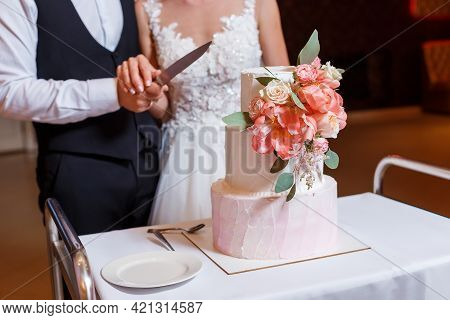 Groom In Suit And Bride In White Dress Cut Beautiful Multi Level Wedding Cake, Decorated With Cream,