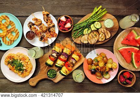 Vegan Summer Bbq Or Picnic Table Scene. Top View Over A Dark Wood Background. Grilled Fruit And Vege