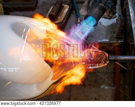 Master Glassmaker Heats A Fire Torch Glass Ball On A Glass Pipe. Hand Shaping Hot Glass In A Glass D