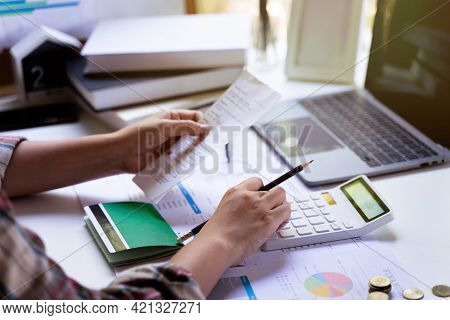 Accounting Concept. Businesswoman Using A Calculator To Calculate Bill Income Expenditure, Savings A
