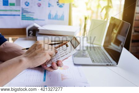 Businessman Or Man Entrepreneur Holding Pencil And Using A Calculator To Calculate Financial Expense