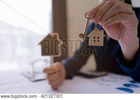 Real Estate Agent Sales Manager Holding Keys To Customer And Holding Sign House Offer For And House