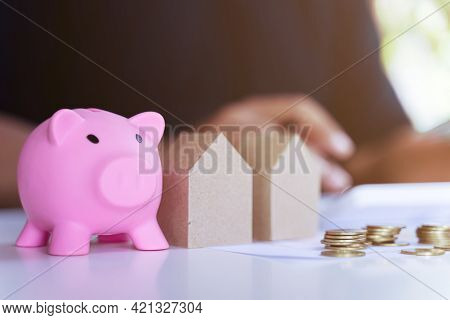 The Personal Saving Financial Concept For Own A House. Piggybank And House Model And Banker Or Offic