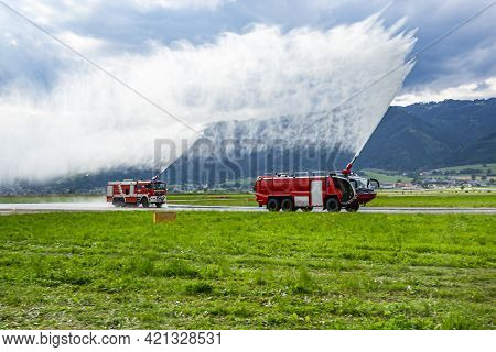 Zeltweg, Austria - June 29, 2013: Fire Fighting With Water Spray. Fire Truck And Fire Engine With Fi