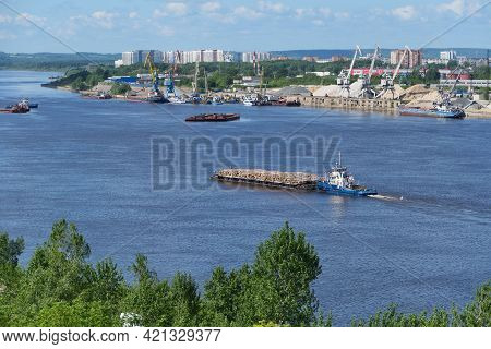 A Barge Carries Cargo On The River. Transportation Of Wood By River Cargo Transport. In The Backgrou
