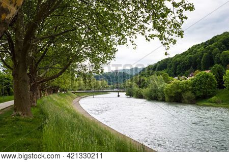 View At The Savinja River With Old Castle On A Hill In The Background In Celje Under Overcast Sky In