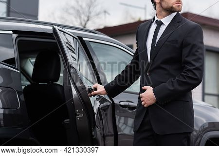 Partial View Of Bearded Bodyguard With Security Earpiece Opening Car Door.
