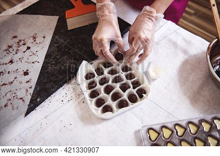 Top View Of Chocolatier Hands In White Transparent Gloves Packing Chocolate Truffles In Box Lying Ne