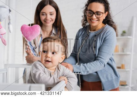 Blurred And Happy Interracial Women Looking At Infant Boy In Baby Crib In Bedroom.