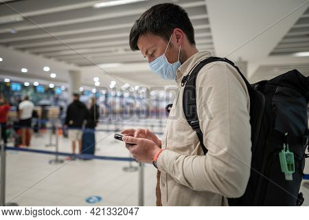 Male Passenger In Mask With Backpack Uses Smartphone And Stands With Social Distance On Check-in Lin