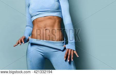 Close Up Of Perfect Abdominal Muscles Of Fitness Woman In Blue Sports Suit. Unrecognizable Sexy Spor