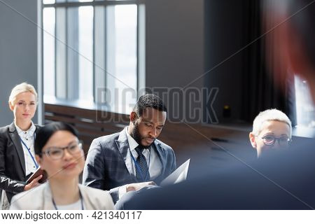 Multicultural Participants Sitting In Conference Room Near Lecturer On Blurred Foreground.