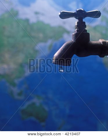 A Drop Of Water Falls From A Faucet Over A Map