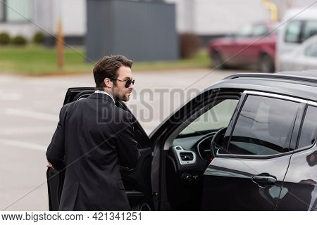 Bearded Bodyguard In Suit And Sunglasses With Security Earpiece Near Opened Door Of Modern Auto.