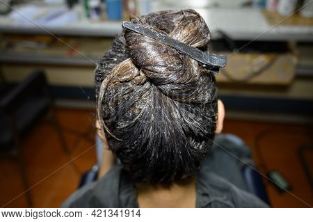 Top View Of Woman Back Head During Hair Coloring Process In Barber Shop. Hair Coloring Process Is To