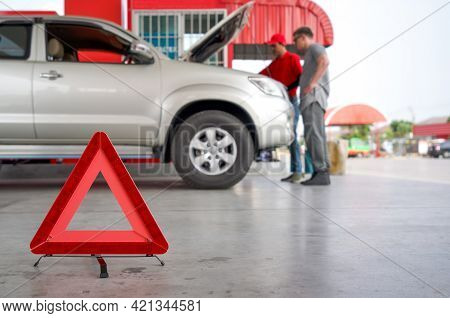 Red Triangle Reflector Roadside Warning On The Floor. There Is A Broken Pickup Car In The Background