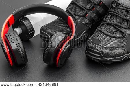 Sneakers With Headphones And Bottle For Water On Black.