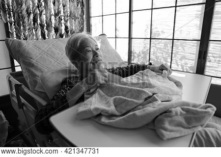 A Senior Woman With Dementia Lying Down On The Nursing Bed Playing With A Blanket