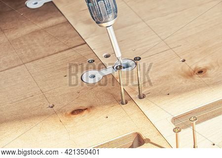 Employee Assembles New Wooden Dining Table Turning Screws With Electric Screwdriver Outdoors On Sunn