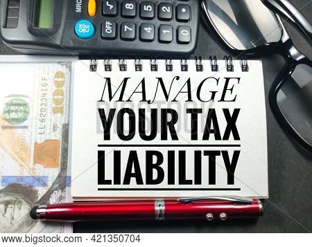 Business Concept.text Manage Your Tax Liability With Glasses,pen,calculator And Banknote On Black Ba
