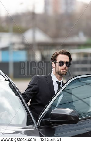 Bearded Bodyguard In Suit And Sunglasses With Security Earpiece Sitting In Modern Car.