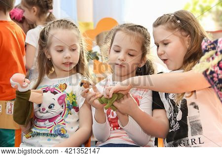 Omsk, Russia - September 16, 2020. Group Of Three Cute  Blonde Girls Enthusiastically Play Finger Pu