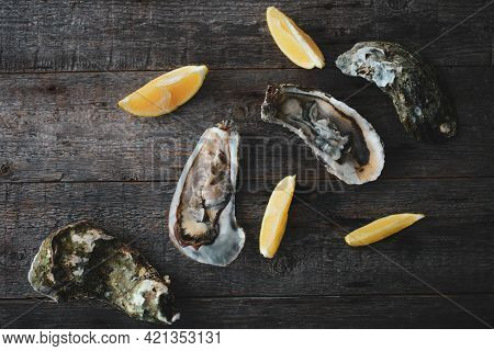 Close-up Of Fresh Open Raw Oysters With Lemon And Ice On A Wooden Background. Healthy Seafood. View