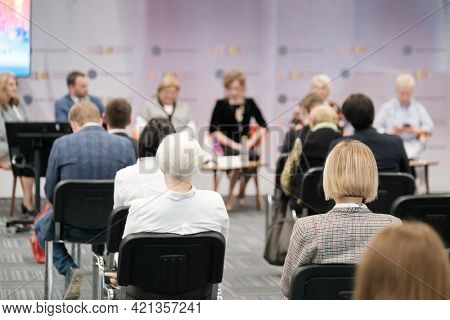 Unrecognizable female speaker standing and explaining business ideas to entrepreneurs gathering in conference auditorium