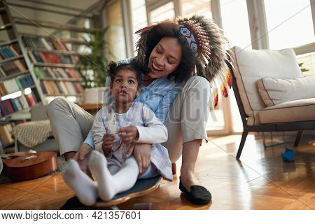 A young Mom with an indian headdress rides on the skateboard with her little daughter in a cheerful atmosphere at home. Family, together, love, playtime