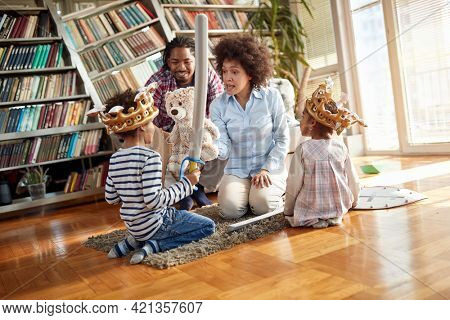 Young parents talking to their children while playing in family atmosphere at home together. Family, together, love, playtime