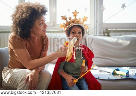 A young Mom is feeding her little son with the banana while playing in a relaxed atmosphere at home together. Family, together, love, playtime