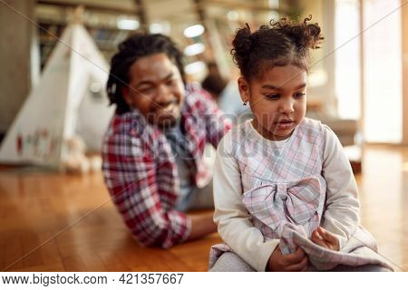 A sweet little thoughtful girl playing with her father on the floor in a cheerful atmosphere at home. Family, together, love, playtime