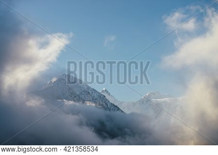 Beautiful View Of Snow-capped Mountains Above Thick Clouds In Sunshine. Scenic Bright Mountain Lands