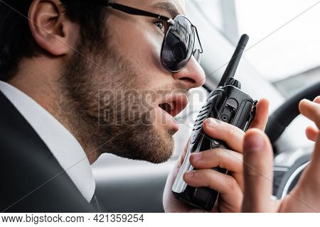 Close Up Of Bearded Bodyguard In Sunglasses Using Walkie Talkie In Car.