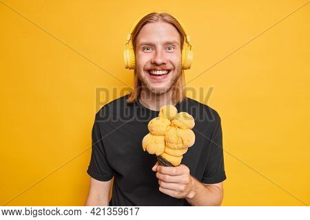 Youth And Lifestyle Concept. Positive Redhead Hipster Guy Holds Big Tasty Ice Cream Of Mango Flavor