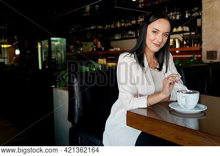 Beautiful Girl Drinking Coffee In Cafe. Beauty Woman With Cup Of Hot Beverage